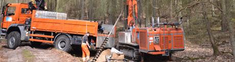 Ein Bohrgerät und LKW in einem Wald. Zu sehen ist auch das Schneckenbohrgestänge von ca. 1m Länge.