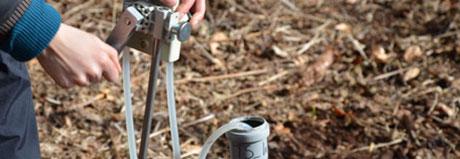 feldarbeit: grundwassermessungen in einem grundwasserpegel aus plastik mit einem schlauch